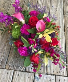 Red, deep pink, purple and green flowers in a charming container.