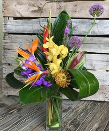 Heliconia and orchids in a clear glass vase.