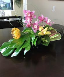 Cymbidium orchids and greenery in an elegant centerpiece design.