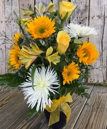 Cheerful yellow and white flowers in a clear glass vase.