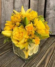 Yellow flowers in a clear glass vase with lemon.