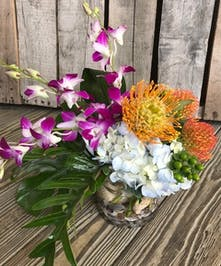 Orchids, hydrangea and protea with greenery in a clear glass vase accented with sea shells.