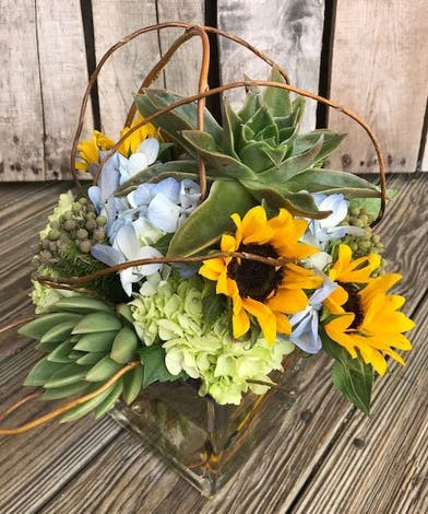 Sunflowers, hydrangea and succulents in a glass vase.
