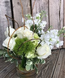 A refreshing touch of green nestled next to cream roses, large, white hydrangea and fragrant stock blooms.