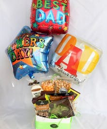 Gift basket filled with chocolate, snacks and more tied with three mylar balloons.