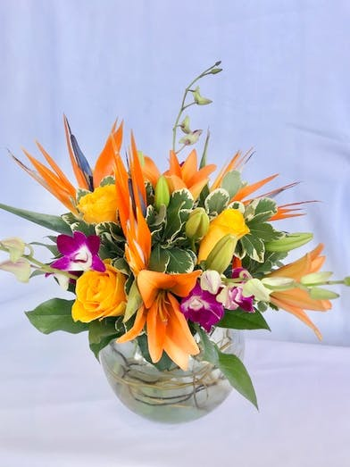 Orchids, birds of paradise and other tropical flowers in a clear glass bubble bowl vase.