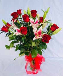 Lilies and roses in a clear glass vase tied with red ribbon