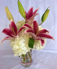 White hydrangea and pink lilies in a clear glass vase.