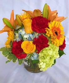 Carnations, gerbera daisies, roses, and hydrangea in a clear glass vase.