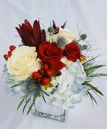 Blue hydrangea, white roses and hypericum berries with red roses in a clear glass cube vase.