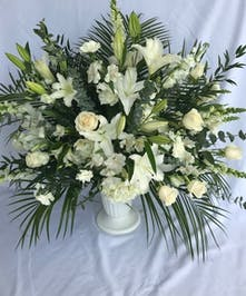 All-white sympathy arrangement presented in a white urn.