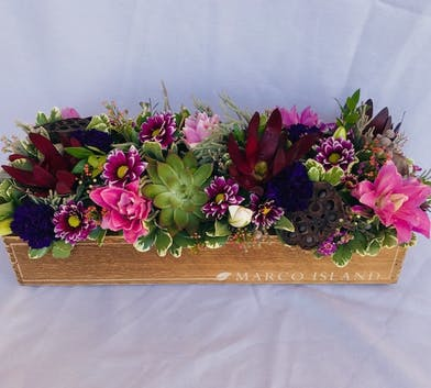 Wooden trough filled with pink and red flowers and succulents.