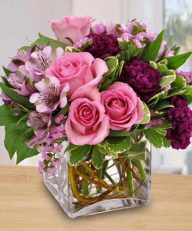 Glass cube filled with long lasting flowers in shades of purple.