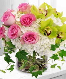 Short cylindar vase filled with orchids, roses and hydrangea.