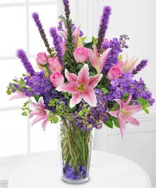 A tall glass vase filled with purple and pink flowers.