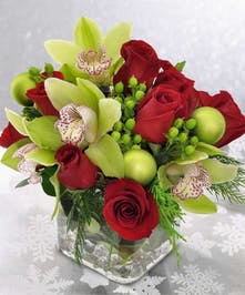 Glass cube filled with red roses and green cymbidium orchids in a compact design.