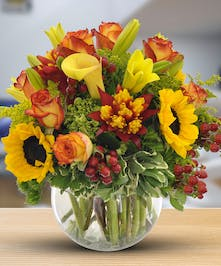 Sunflowers, circus roses, lilies, berries and greenery in a glass bubble bowl vase.