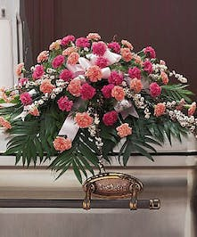 Casket spray of dark and light pink carnations and greenery.