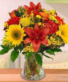 Glass vase of lilies, sunflowers, roses and alstroemeria