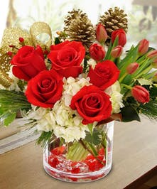 Glass vase of tulips, hydrangea and roses clustered together with pinecones