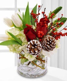 Bouquet of red and white flowers with pine cone and berry accents.