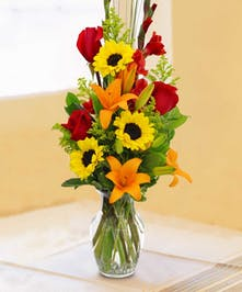 Red, yellow and orange flowers in a clear glass vase.