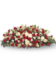 Casket spray made of red and white flowers.