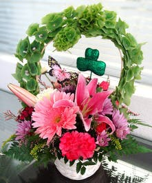 Pink and green flowers in a basket with shamrock and butterfly decorations.