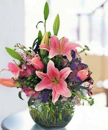 Stargazer lilies roses, stock and alstroemeria in a glass bowl vase.