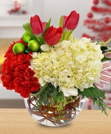 Red and white flowers in a clear glass bowl accented with holiday ornaments