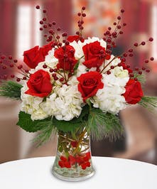 Glass vase of white hydrangea, red roses, pine cones and berries.