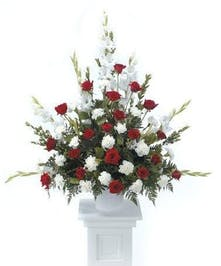 Traditional sympathy basket of red roses, white carnations and white glads.