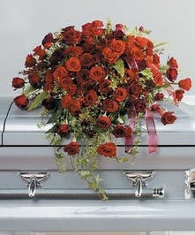 Casket flowers featuring mixed red flowers in a bed of greenery.