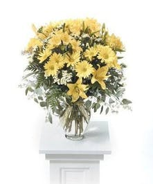 Glass vase filled with yellow daisies, alstroemeria and lilies.