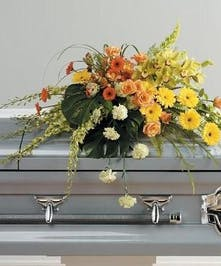 Casket spray of yellow, orange and green flowers including cymbidium orchids and roses.