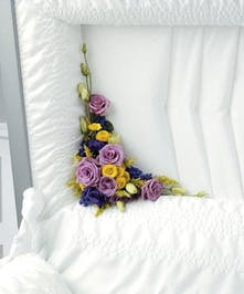 Casket lid corner adornment of purple and yellow flowers.