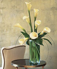 White calla lilies in a tall glass cube vase.