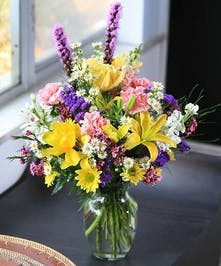 Bright spring flowers in a clear glass vase.