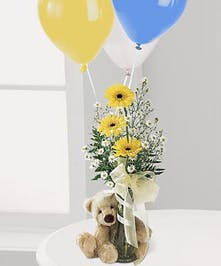 Yellow and white flowers in a clear bud vase accompanied by a plush teddy bear and latex balloons.