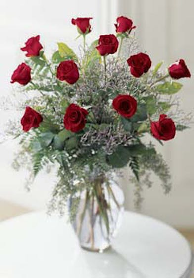 One dozen long stemmed red roses with caspia in a clear glass vase.