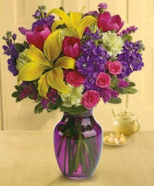Bright yellow, purple and pink flowers in a purple vase.