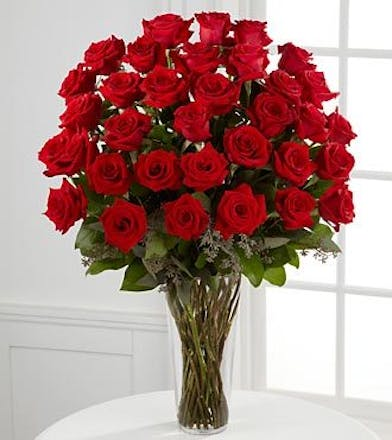 36 Ecuadorian red roses arranged in a glass vase with greenery.