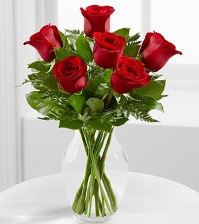 Six red roses and greenery in a clear glass vase.