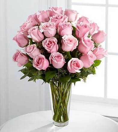 Two dozen pink roses with greenery in a clear glass vase.