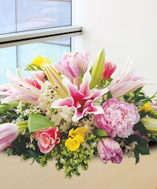 Lilies, peonies, freesia and other pink flowers in a centerpiece for Easter.