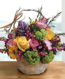 Purple, yellow, green and pink flowers in a handbasket.