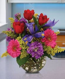 Bright red, pink and purple flowers in a glass bowl vase.