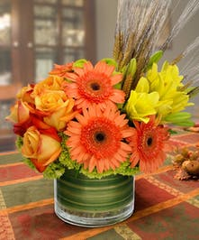 Gerbera daisies, roses, lilies and wheat accents in a leaf-lined cylinder vase.