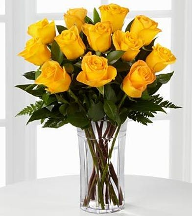 One dozen yellow roses in a clear glass vase with baby's breath.