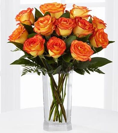 One dozen orange roses and greenery in a clear glass vase.
